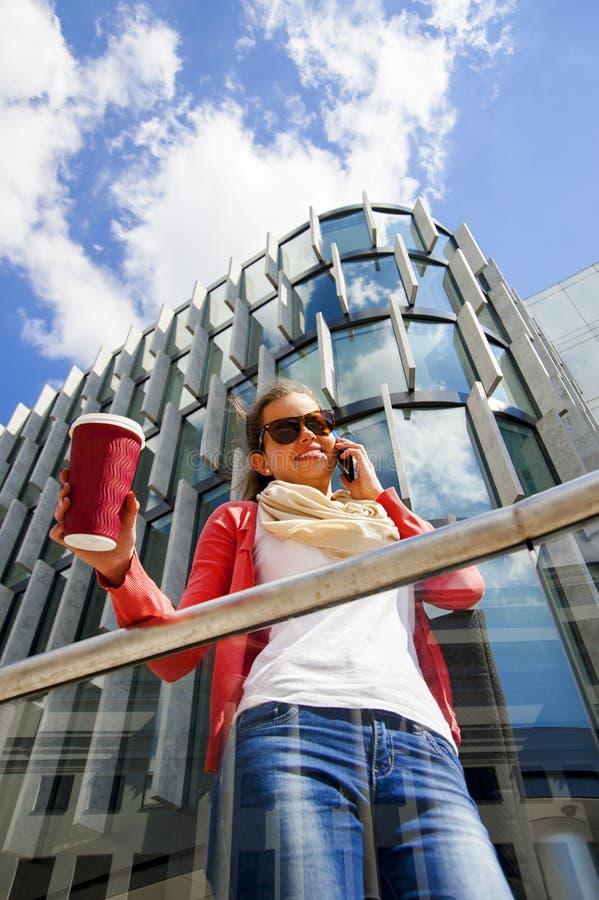 Giovane donna graziosa che per mezzo della tazza del coffe della tenuta del telefono cellulare fotografie stock libere da diritti
