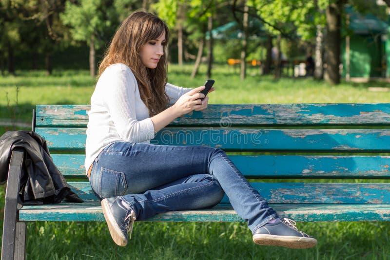 Giovane donna graziosa che per mezzo dello smartphone che si siede sul banco immagini stock
