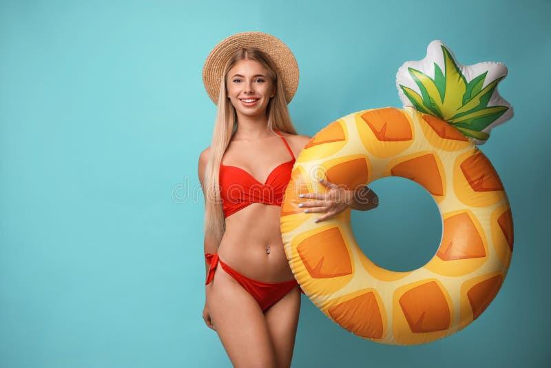 Giovane donna graziosa che porta bikini alla moda con l'anello gonfiabile sul blu fotografia stock