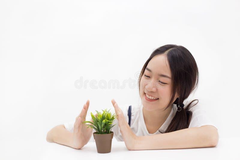 Giovane donna graziosa che protegge e che coltiva una pianta in isola bianco immagine stock libera da diritti