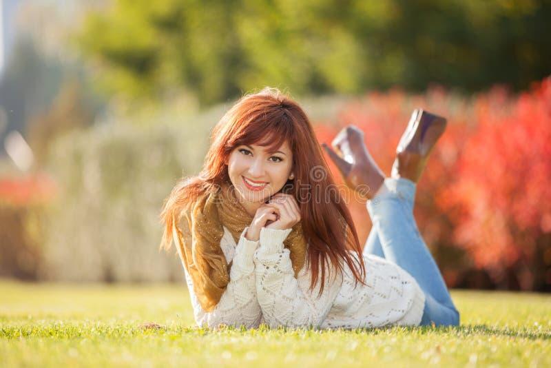Giovane donna graziosa che si rilassa nel parco immagine stock