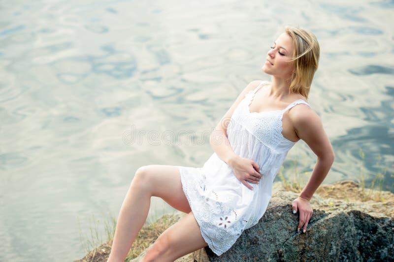 Giovane donna graziosa che si rilassa sul fiume vicino di pietra Giovani adulti fotografie stock