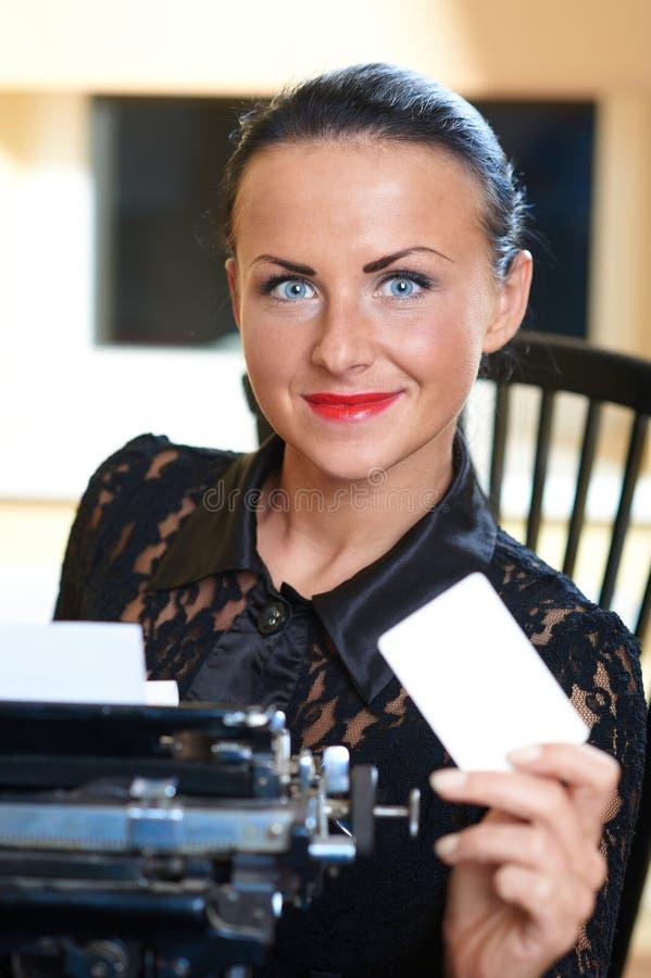 Giovane donna graziosa che si siede ad una macchina da scrivere immagini stock