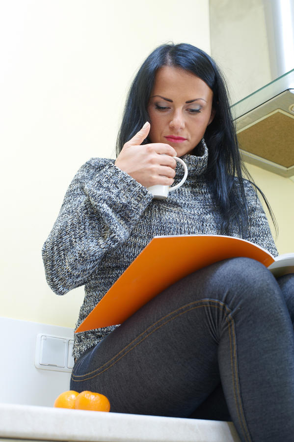 Giovane donna graziosa che si siede su una tabella immagine stock