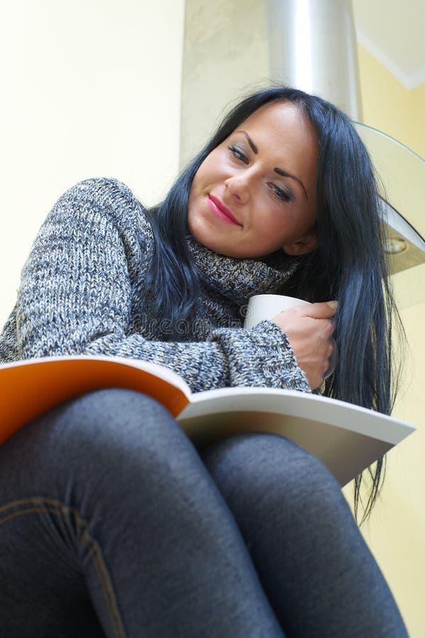Giovane donna graziosa che si siede su una tabella fotografie stock libere da diritti