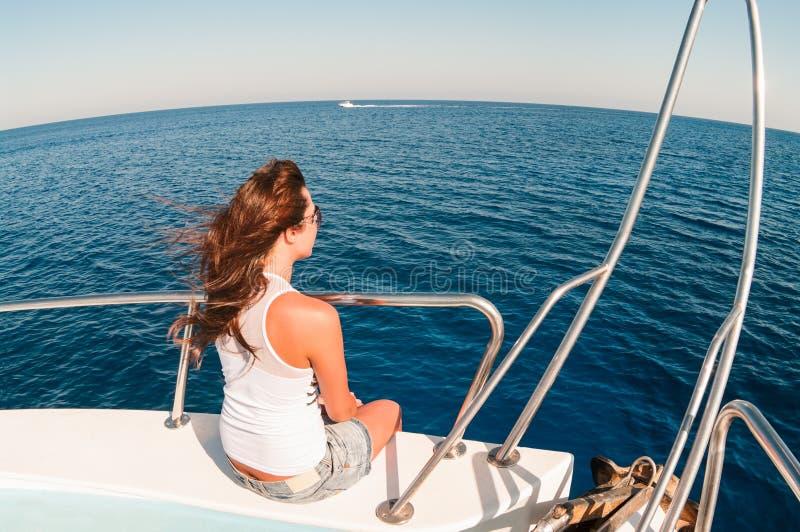 Giovane donna graziosa che si siede sulla fiancata della nave immagini stock libere da diritti
