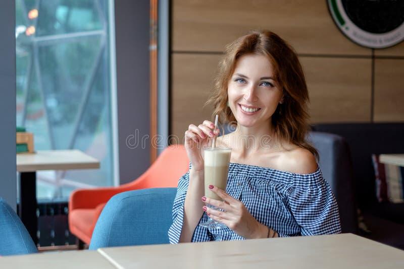 Giovane donna graziosa che si siede in un caffè con un latte della tazza di caffè fotografia stock