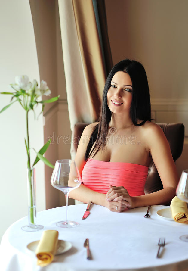 Giovane donna graziosa che si siede in un ristorante fotografia stock