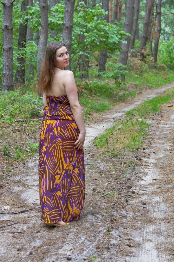 Giovane donna graziosa che sta sul sentiero forestale immagini stock