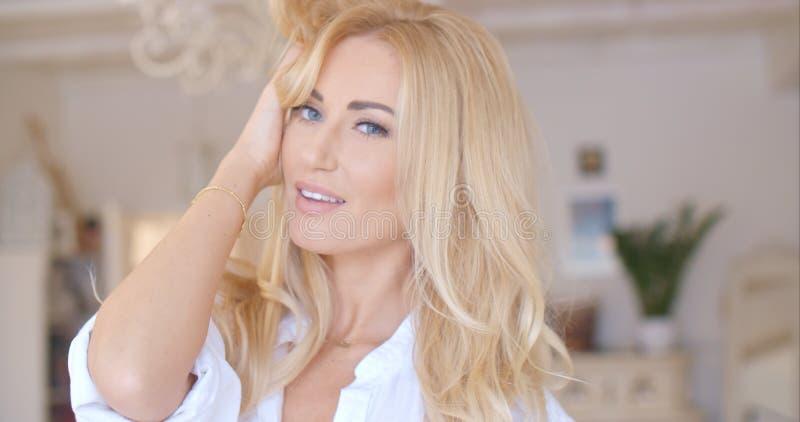 Giovane donna graziosa che tiene i suoi capelli biondi lunghi fotografia stock