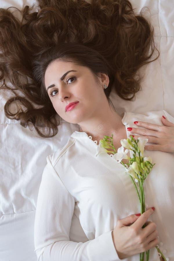 Giovane donna graziosa, con bei capelli lunghi che si trovano sul letto fotografia stock libera da diritti
