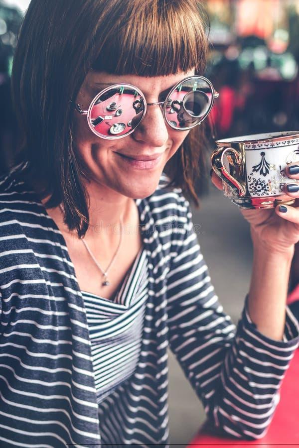 Giovane donna graziosa con gli occhiali da sole che beve caffè in ristorante fuori del terrazzo Isola di Bali fotografie stock