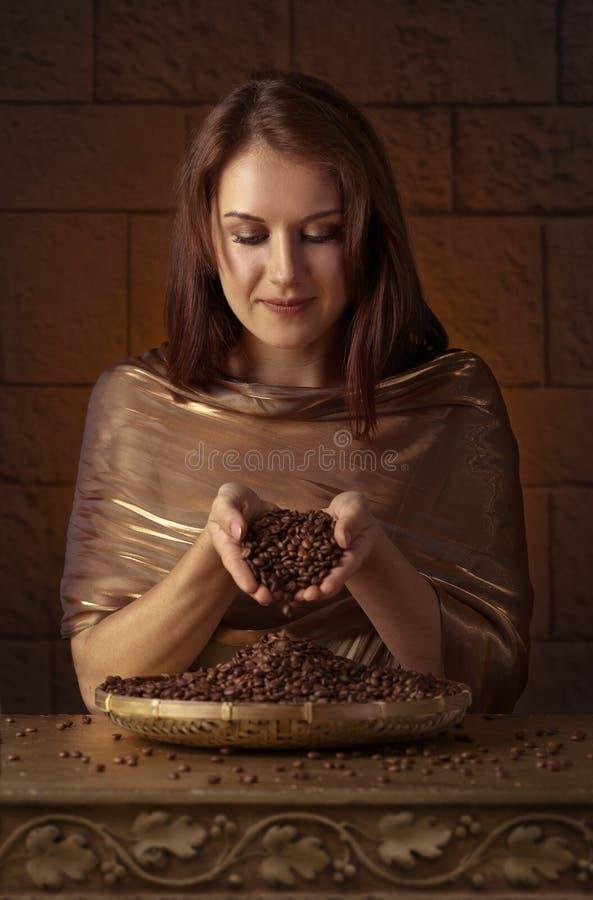 Giovane donna graziosa con i chicchi di caffè fotografie stock libere da diritti