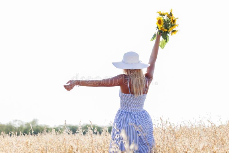 Giovane donna graziosa con il cappello ed il mazzo dei girasoli immagini stock