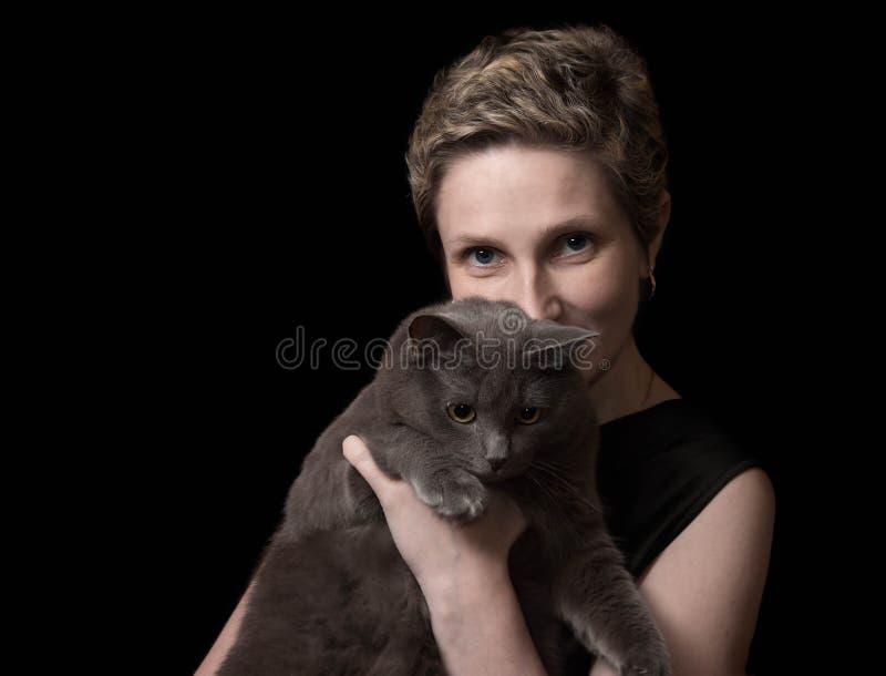 Giovane donna graziosa con il suo gatto fotografia stock libera da diritti