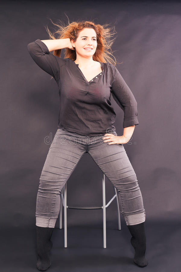 Giovane donna graziosa con sovrappeso che si siede su uno sgabello da bar immagini stock