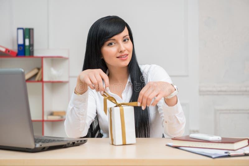 Giovane donna graziosa di affari che si siede allo scrittorio immagini stock