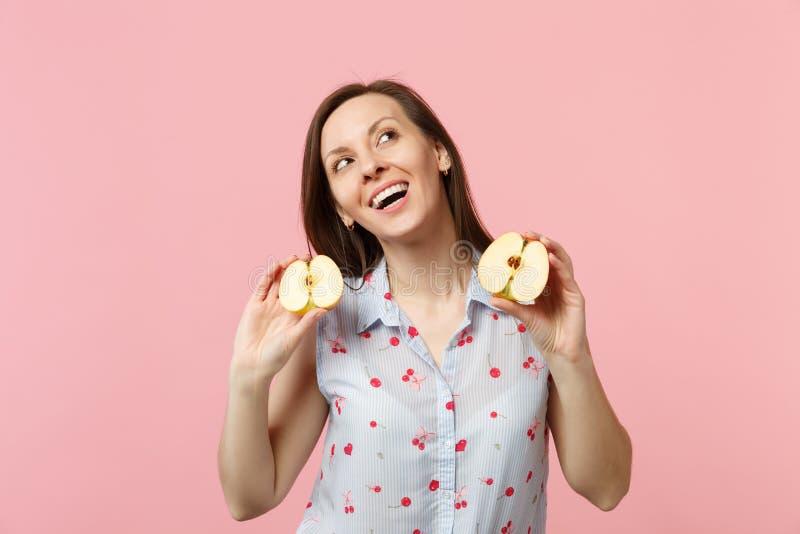 Giovane donna graziosa di Dreamful in vestiti di estate che cerca tenente i halfs della frutta matura fresca della mela isolata s fotografia stock libera da diritti