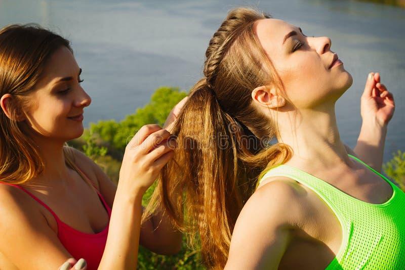 Giovane donna graziosa due che fa acconciatura all'aperto fotografia stock