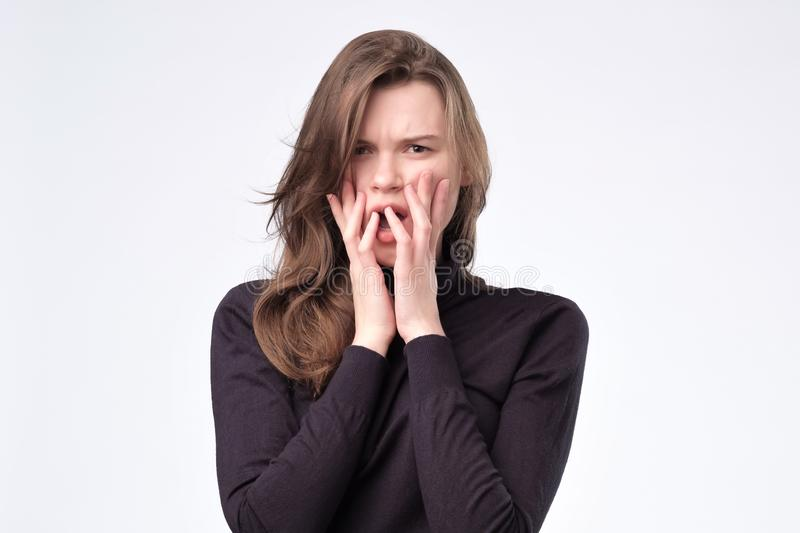 Giovane donna graziosa europea spaventata, impaurita ed ansiosa mordendo le sue unghie del dito fotografie stock