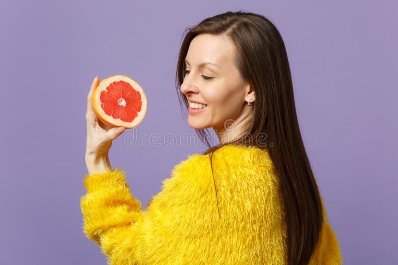 Giovane donna graziosa in maglione della pelliccia che tiene metà disponibila del pompelmo maturo fresco sulla parete pastello vi fotografia stock