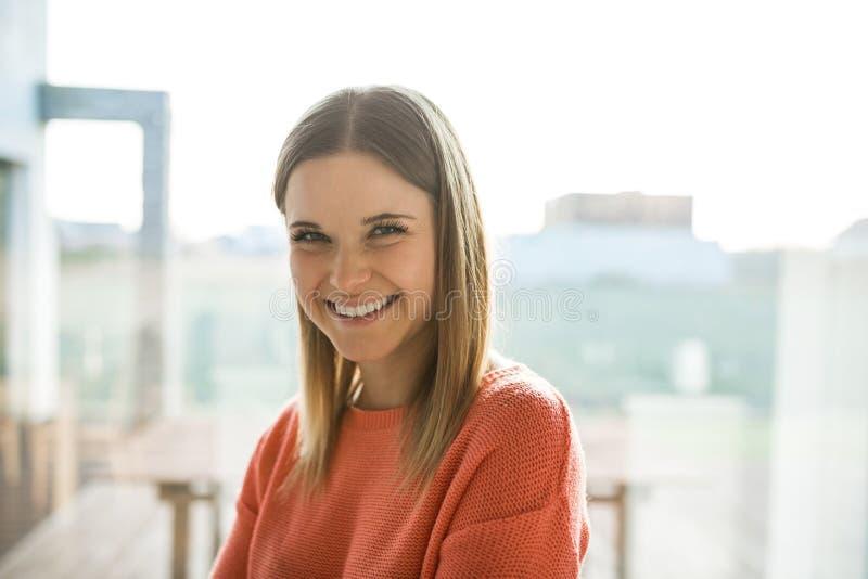 Giovane donna graziosa nella risata rossa del maglione fotografie stock libere da diritti