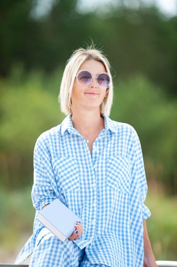 Giovane donna graziosa in occhiali da sole che tengono libro che gode del giorno di estate fotografie stock libere da diritti