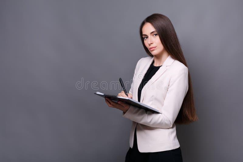Giovane donna graziosa pensierosa di affari che fa le note sul lavoro immagine stock
