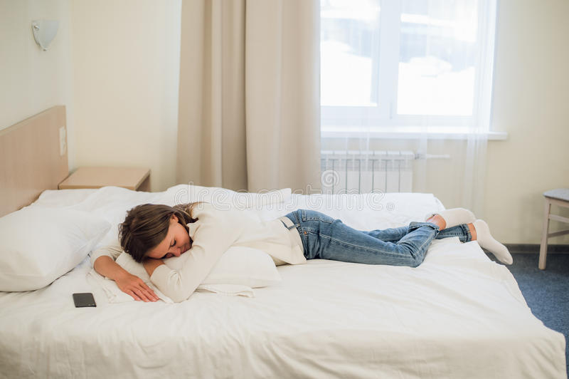 Giovane donna graziosa rilassata che dorme a letto con il telefono cellulare dello schermo in bianco fotografia stock libera da diritti