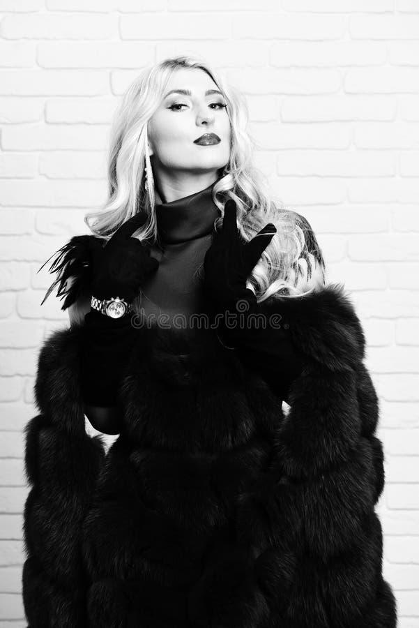 Giovane donna graziosa sexy alla moda con bei capelli biondi ricci lunghi in cappotto della vita della pelliccia di Borgogna e de fotografia stock libera da diritti