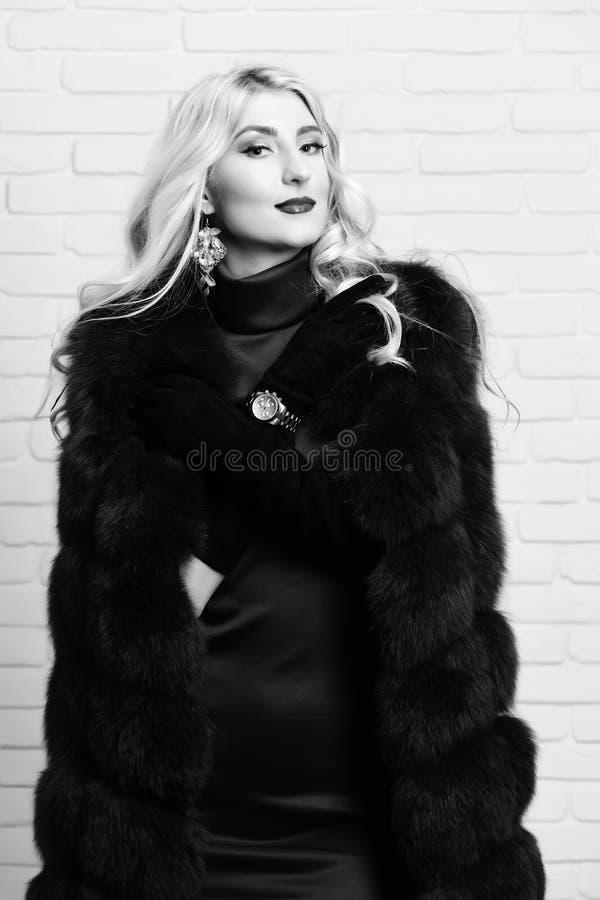 Giovane donna graziosa sexy alla moda con bei capelli biondi ricci lunghi in cappotto della vita della pelliccia e del vestito di immagine stock libera da diritti