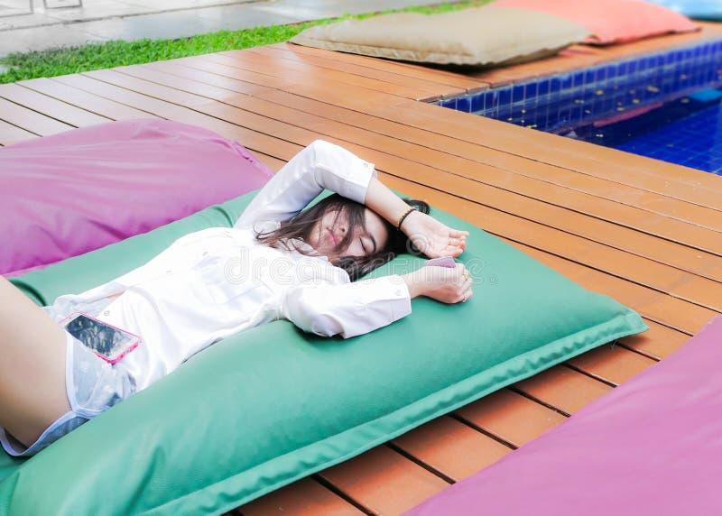 Giovane donna graziosa sorridente che si rilassa sul waterbed su del terrazzo dello stagno dell'hotel immagine stock libera da diritti