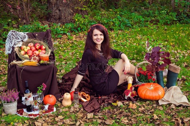 Giovane donna graziosa sorridente che si siede vicino alle verdure nell'Au fotografia stock libera da diritti
