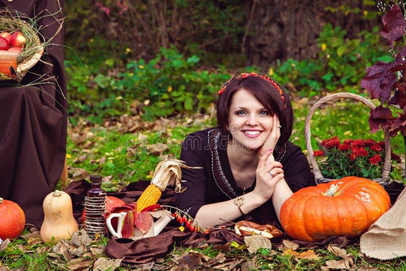 Giovane donna graziosa sorridente che si trova vicino alle verdure nel autu fotografia stock