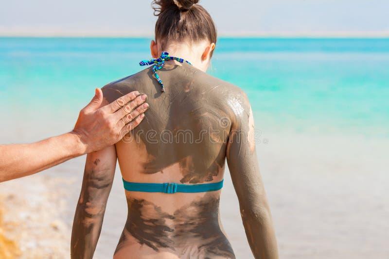 Giovane donna graziosa spalmata di fango sulla spiaggia immagini stock