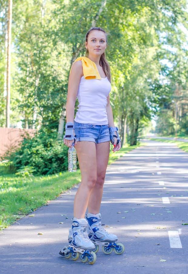 Giovane donna graziosa sui pattini di rullo fotografie stock libere da diritti