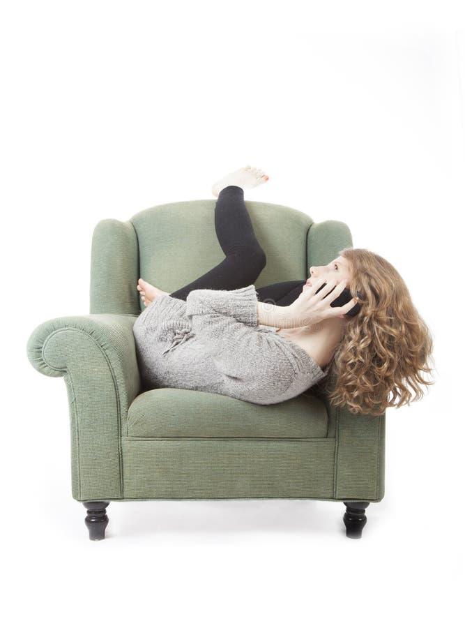 Giovane donna graziosa sul telefono in poltrona fotografia stock