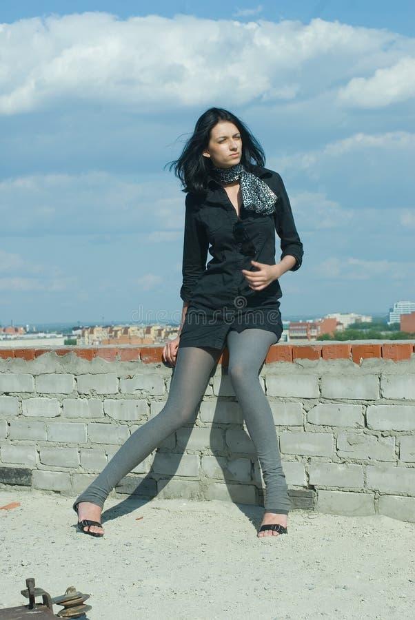 Giovane donna graziosa sul tetto nel giorno di estate immagine stock
