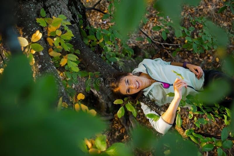 Giovane donna graziosa in un albero che spende tempo in natura fotografia stock