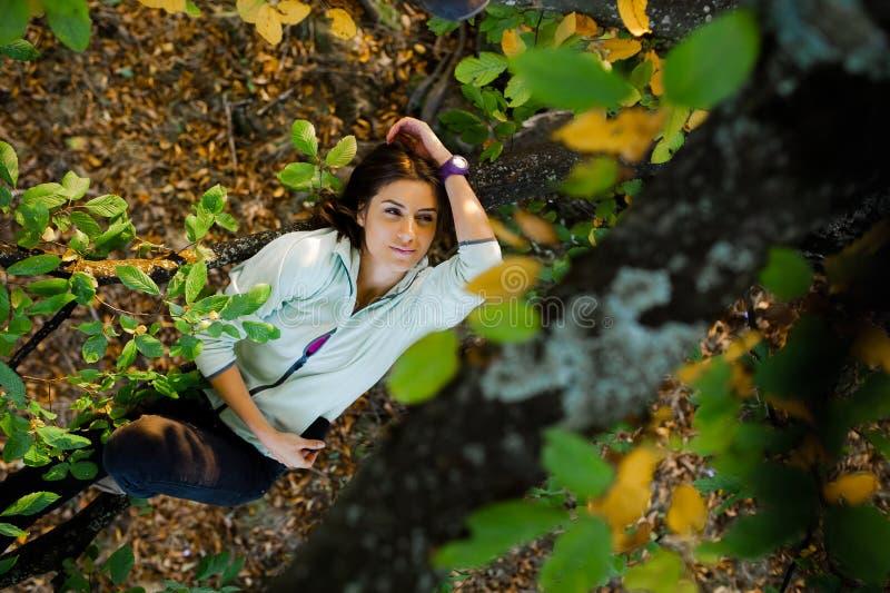 Giovane donna graziosa in un albero che spende tempo in natura fotografia stock libera da diritti