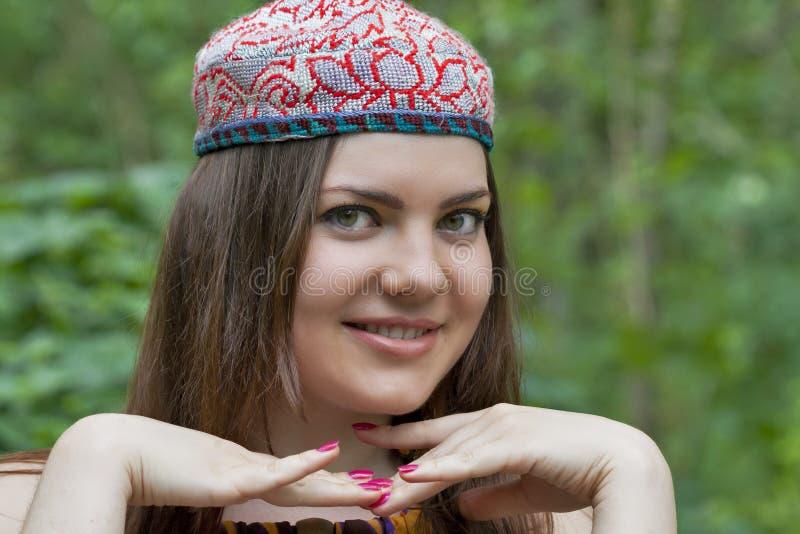 Giovane donna graziosa in uno zucchetto dell'Uzbeco fotografie stock libere da diritti