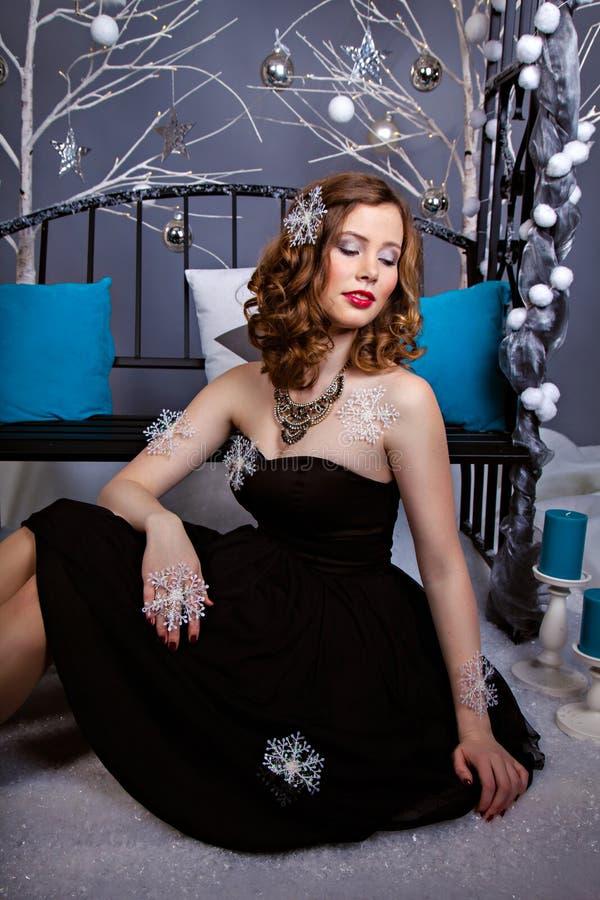 Giovane donna graziosa in vestito da sera con i fiocchi di neve fotografie stock