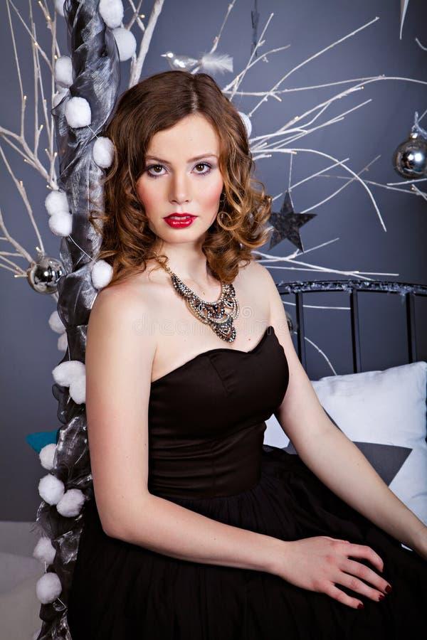 Giovane donna graziosa in vestito da sera fra la decorazione di Natale immagine stock libera da diritti