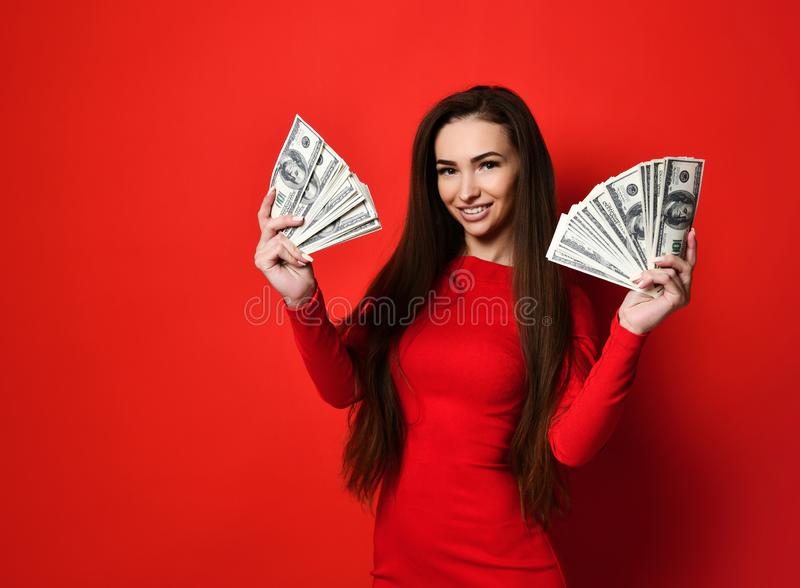 Giovane donna graziosa in vestito rosso che si nasconde dietro il mazzo di banconote dei soldi immagini stock libere da diritti