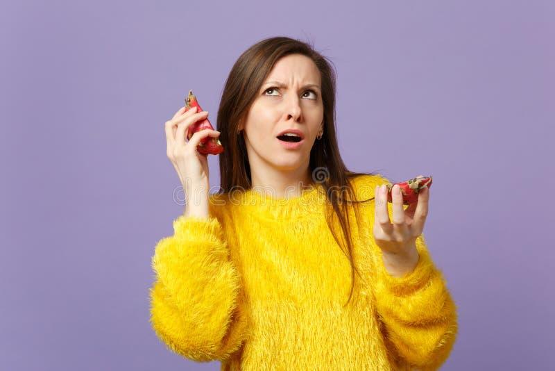 Giovane donna imbarazzata in maglione della pelliccia che cerca tenente i halfs del pitahaya, frutta del drago vicino alle orecch fotografie stock
