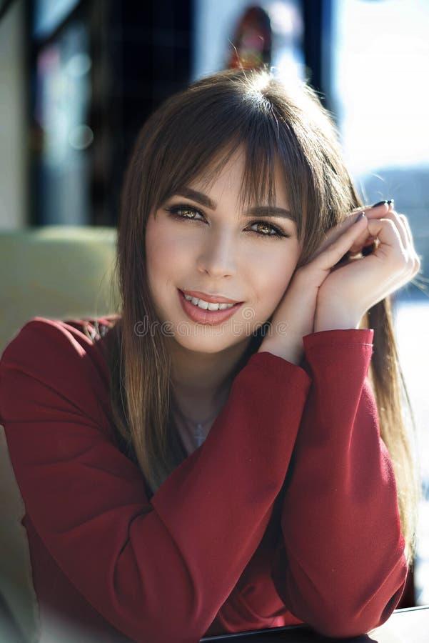 Giovane donna incantante con il sorriso amichevole, caff? sorridente del ritratto dei capelli castana lunghi immagini stock libere da diritti