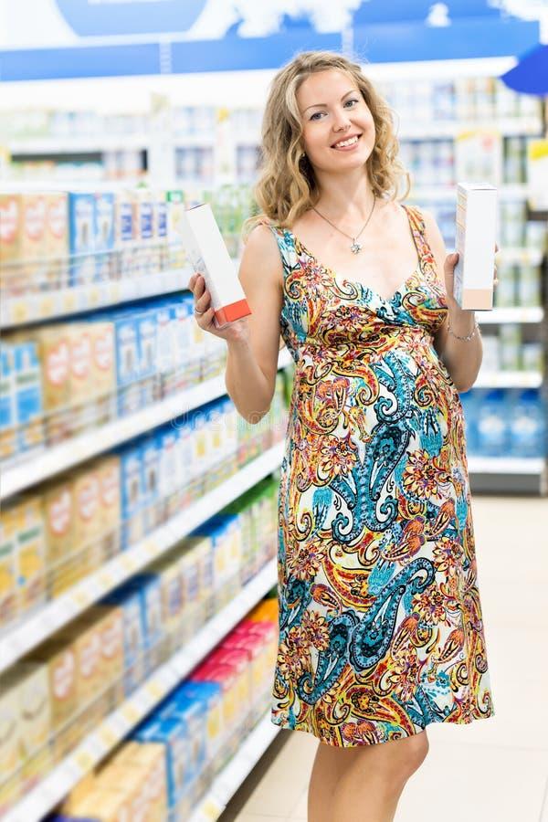 Giovane donna incinta ad acquisto nel deposito del supermercato della latteria fotografie stock