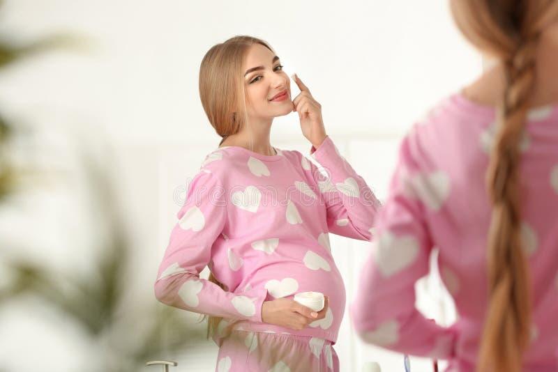 Giovane donna incinta che applica crema su pelle in bagno immagine stock