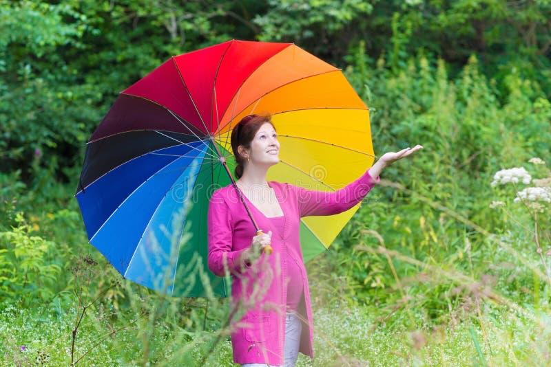 Giovane donna incinta che cammina sotto l'ombrello variopinto fotografia stock
