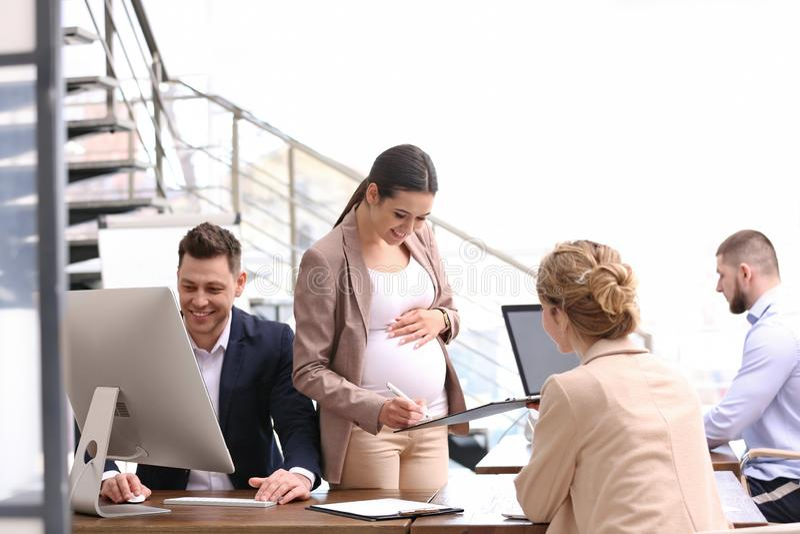 Giovane donna incinta che lavora con i suoi impiegati fotografia stock